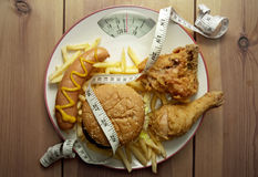 Junk food diet weighing scales Royalty Free Stock Images
