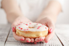 Junk-food and eating concept - close up of female hand holding glazed donut Royalty Free Stock Photos