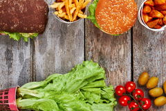 Junk food and fresh vegetables. Olives, cherry tomatoes and fries. Make your choice Stock Photos