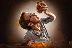 Junk Food. Man eats greasy fast food Royalty Free Stock Image