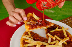 Junk food. Pouring ketchup on pizza garnished with french fries, a  junk food concept Royalty Free Stock Image