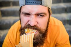 Junk food. Snack for good mood. Unleashed appetite. Street food concept. Man bearded eat tasty sausage. Urban lifestyle. Nutrition. Carefree hipster eat junk royalty free stock images