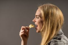 Junk food and unhealthy eating concept. Portrait of young woman who holding fried potato chips at the mouth. Posing over gray background. Studio shot stock photo