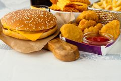 Assortment of fast food. Junk food on white table. Fast carbohydrates not good for health, heart and skin Stock Images