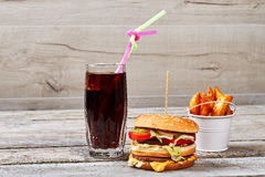 Junk food on wooden backdrop. Fried potatoes, burger and soda. Stop eating unhealthy food Royalty Free Stock Photography