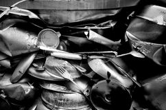 Junk pile up of old compressed utensils and pots in iblack and Stock Photos