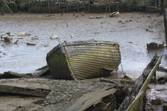 Decaying boat on mud flats. A boat left abandoned on the mud flats beside a river Royalty Free Stock Photography