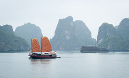 A junk sails through Halong Bay Stock Photos
