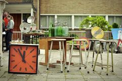 Junk for sale at the King's day market. April 2014, Apollolaan, Amsterdam. An orange colored retro wall clock, four bar chairs and some soda bottle showcased at Royalty Free Stock Images