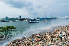 Junk yard area view full of smoke, litter, plastic bottles,rubbish and trash at the Thilafushi local tropical island. Junk yard area view full of smoke,litter Stock Photo