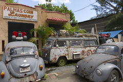 Junk yard with old Volkswagen cars. SAN JUAN, PUERTO RICO - MARCH 13, 2015: Junk yard adjacent to a coin laundry business in Tras Talleres neighborhood holds royalty free stock photos