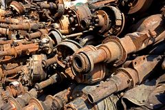 Junk Yard Scrap Rusty Axels and Drive Shafts. Image from an industrial sector or truck graveyard or scrap metal park of a stack of old large axels with wheel Stock Images