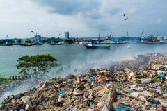 Junk yard zone view full of smoke, litter, plastic bottles,rubbish and trash at the Thilafushi local tropical island. Junk yard zone view full of smoke,litter Royalty Free Stock Image