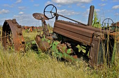 Junked tractor lacking parts and tires. An old tractor without tires and missing others parts is left abandoned in a salvage and junkyard Royalty Free Stock Photography