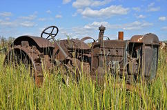 Junked tractor lacking parts and tires. An old tractor without tires and missing others parts is left abandoned in a salvage and junkyard Stock Photography