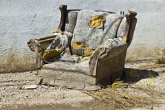 Junked, trashed and ruined upholstered chair ready to be taken to the landfill Stock Photography