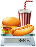 Junkfood on the scale Stock Image