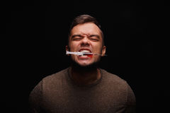 A junkie with drug addictions clamps between teeth a syringe with an injectable drug on a dark black background. A drug user with addiction clamps a syringe royalty free stock photos