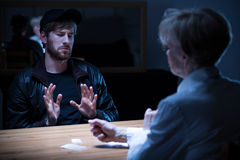 Junkie man interrogated by policewoman stock photo