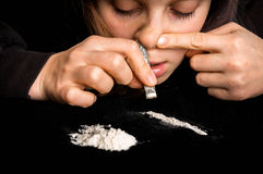 Junkie woman snorting cocaine powder with rolled banknote. On black background Royalty Free Stock Photo