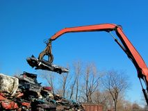 Junkyard crane with claw and crushed car royalty free stock photography