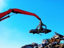 Junkyard crane with claw and crushed car stock image