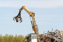 Junkyard crane with maginet moving scrap recycled steel royalty free stock photos