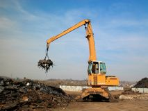Junkyard crane with maginet. Moving scrap recycled steel stock photos