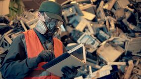 Junkyard employee in a respirator is working with a tablet