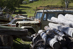 Junkyard with logs and old agricultural machinery Royalty Free Stock Image