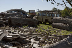 Junkyard with logs and old agricultural machinery stock image