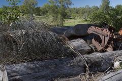 Junkyard with logs and old agricultural machinery Stock Photos