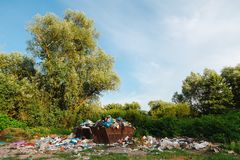 Junkyard in then nature - Containers full of trash - no separation. stock images