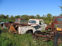 Junkyard Trucks. A row of trucks sitting rusting away in a junkyard Stock Photo