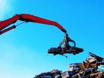 Junkyard żuraw z pazurem i zdruzgotanym samochodem Obraz Stock