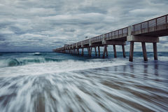 Juno Beach Park Pier. Juno beach twilight tide with dramatic sky and blue waters at Jupiter, Florida, United States stock image