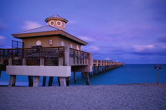 Juno Beach Park Pier. Juno beach twilight tide with dramatic sky and blue waters at Jupiter, Florida, United States stock photography