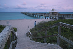 Juno Beach Park Pier. Juno beach twilight tide with dramatic sky and blue waters at Jupiter, Florida, United States royalty free stock photography
