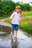 Junps da menina com os pés descalços em uma poça Foto de Stock Royalty Free