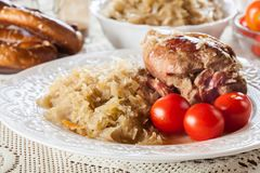 Junta da carne de porco com chucrute e os tomates fritados fotos de stock