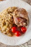 Junta da carne de porco com chucrute e os tomates fritados imagem de stock royalty free