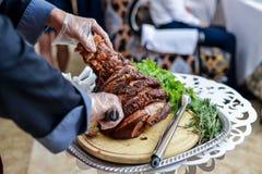 Junta da carne de porco nas mãos do cozinheiro do cozinheiro chefe Prato quente no close-up da mesa de cozinha Fotos de Stock Royalty Free