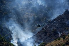 Junta De Andalucia helicopter Bell 212 taking water to douse wildfire between Sayalonga and Arenas, Spain. Royalty Free Stock Images
