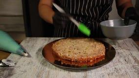 Junta de las capas de la torta del nuez-plátano, manchando con el jarabe, el proceso entero almacen de metraje de vídeo