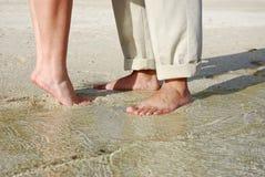 Junta los pies que se colocan en la playa Imagenes de archivo