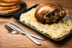 A junta Roasted da carne de porco serviu com o chucrute no fundo de madeira Imagens de Stock