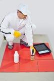 Juntas de la pintura de fondo del cepillo del trabajador de azulejos rojos Fotos de archivo