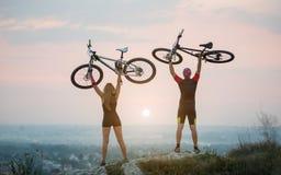 Junte al ciclista con las bicis de montaña en la colina en la puesta del sol imágenes de archivo libres de regalías