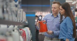 Junte al hombre y la mujer elige la caldera eléctrica en la tienda almacen de metraje de vídeo