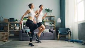 Junte al hombre y mujer que corren sobre el terreno en casa y ejercicio móvil de los brazos metrajes